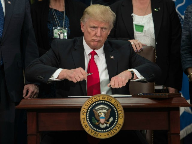 US President Donald Trump takes the cap off a pen to sign an executive order to start the Mexico border wall project at the Department of Homeland Security facility in Washington, DC, on January 25, 2017. / AFP PHOTO / NICHOLAS KAMM (Photo credit should read NICHOLAS KAMM/AFP/Getty Images)