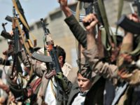 Houthi rebels hold their weapons aloft in Sana'a, Yemen.