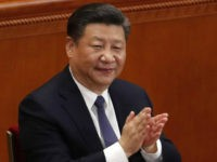 In this Sunday, March 11, 2018, photo, Chinese President Xi Jinping applauds after hearing the results of a vote on a constitutional amendment during a plenary session of China's National People's Congress (NPC) at the Great Hall of the People in Beijing. China's move to scrap term limits and allow …