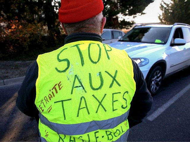 A man wears a Yellow Vest (Gilet jaune) reading 'stop taxes' during a demonstration of the movement against the rising of the fuel and oil prices on November 17, 2018 the entrance of Reims, northern France. - Thousands of drivers blocked roads across France in a 'yellow vest' movement against …