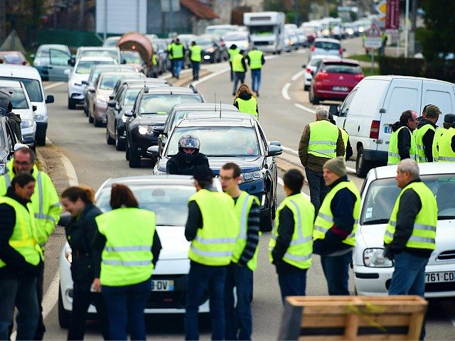 Demonstrators wearing a Yellow Vest (Gilet jaune) block the road during a protest against the rising of the fuel and oil prices on November 17, 2018 in Toulouse, southern France. - Thousands of drivers blocked roads across France on November 17 in a 'yellow vest' movement against high fuel prices …