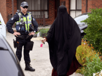 Media question a woman as she enters a house raided by police in the Melbourne suburb of Dallas on November 20, 2018. - Three men who allegedly plotted 'chilling' terror attacks in Melbourne were arrested early November 20, less than two weeks after a stabbing rampage inspired by the Islamic …