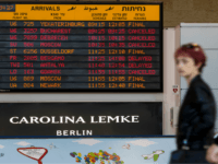 A passenger walks past an information board indicating delayed or cancelled flights during a strike at the Ben Gurion Airport near the Israeli city of Tel Aviv on December 17, 2017. Flights at Israel's main airport were suspended as part of a strike against plans by pharmaceutical giant Teva to …