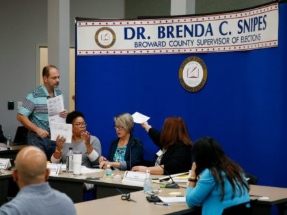 Members of the canvassing board for the Broward County Supervisor of Elections Office review ballots on November 10, 2018 in Lauderhill, Florida. Three close midterm election races for governor, senator, and agriculture commissioner are expected to recounted in Florida. (Photo by Joe Skipper/Getty Images)