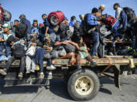 TOPSHOT - Central American migrants -mostly honduran- taking part in a caravan to the US, are pictured on board a truck heading to Irapuato in the state of Guanajuato on November 11, 2018 after spending the night in Queretaro in central Mexico. - The United States embarked Friday on a …