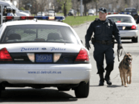 Officer Stephen Speil of the Detroit Police Department's K-9 Unit takes his bomb-sniffing dog 'Radar' to check parked vehicles for explosives at the funeral of rapper Deshaun 'Proof' Holton April 19, 2006 in Detroit, Michigan. Proof's funeral was attented by several thousand people. His solid bronze, 24K gold-plated casket cost …