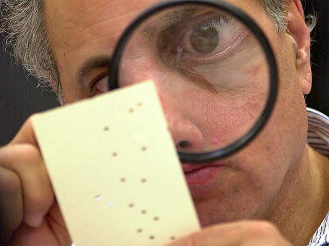 FILE - In this Nov. 24, 2000, file photo, Broward County, Fla. canvassing board member Judge Robert Rosenberg uses a magnifying glass to examine a disputed ballot at the Broward County Courthouse in Fort Lauderdale, Fla. The Founding Fathers set up the Electoral College to ensure a well-informed, geographically diverse …