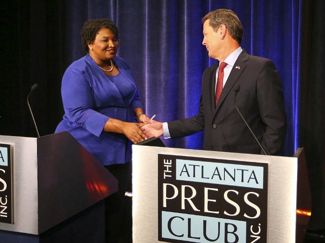 Democrat candidate for Georgia Governor Stacey Abrams, left, and Republican Secretary of State Brian Kemp greet each other before a debate Tuesday, Oct. 23, 2018, in Atlanta. (AP Photo/John Bazemore, Pool)