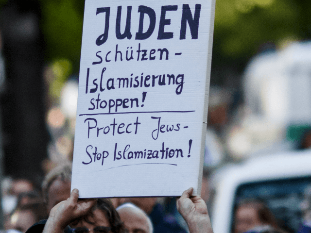 A participant shows a banner during a 'wear a kippah' gathering to protest against anti-Semitism in front of the Jewish Community House on April 25, 2018 in Berlin, Germany. The Jewish community made a public appeal for Jews and non-Jews to attend the event and wear a kippah as a …