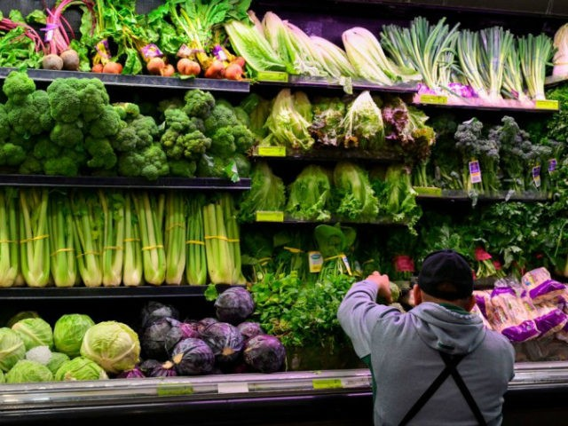A produce worker stocks shelves near romaine lettuce (top shelf center) at a supermarket in Washington, DC on November 20, 2018. - US health officials warned consumers not to eat any romaine lettuce and to throw away any they might have in their homes, citing an outbreak of E. coli …
