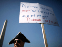 A man stands next to a sign pro-gun rally organized by the Second Amendment March group, near the Washington Monument April 19, 2010 in Washington, DC. Known as Patriots' Day, April 19 is also the anniversary of the American Revolutionary War battles of Lexington and Concord, the Oklahoma City bombing …