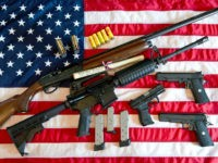 This February 4, 2013 photo illustration in Manassas, Virginia, shows a Remington 20-gauge semi-automatic shotgun, a Colt AR-15 semi-automatic rifle, a Colt .45 semi-auto handgun, a Walther PK380 semi-auto handgun and various ammunition clips with a copy of the US Constitution on top of the American flag. US President Barack …