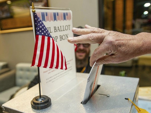 A voter drops an election ballot off at the Pitkin County Administration box in Aspen, Colo., on Tuesday Nov. 6, 2018. (Anna Stonehouse/The Aspen Times via AP)