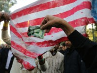 On the eve of renewed sanctions by Washington, Iranian protesters burn a dollar banknote and a US makeshift flag during a demonstration outside the former US embassy in the Iranian capital Tehran on November 4, 2018, marking the anniversary of its storming by student protesters that triggered a hostage crisis …