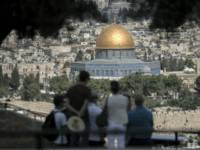 Tourists listen to a guide during a visit at Mount of Olives in east Jerusalem overlooking the Old City and the Dome of the Rock mosque, situated at the Al-Aqsa mosque compound, on June 28, 2016. Israeli authorities announced they were closing Jerusalem's flashpoint Al-Aqsa mosque compound to non-Muslim visitors …