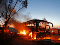 A picture taken on November 12, 2018 shows a bus set ablaze after it was hit by a rocket fired from the Gaza Strip, at the Israel-Gaza border near the kibbutz of Kfar Aza, on November 12, 2018. - Israel's military said it was carrying out air strikes 'throughout the …
