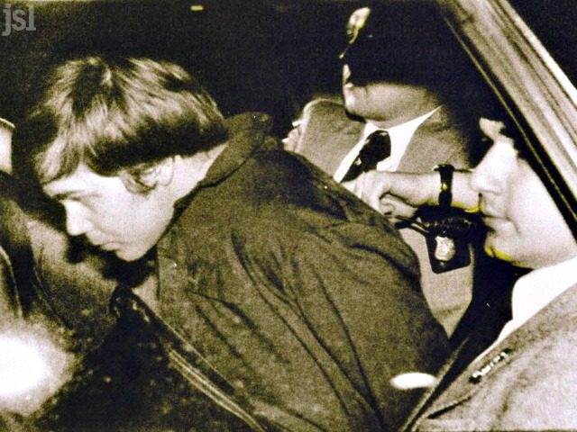 This March 30, 1981 file photo shows John Hinckley Jr. (L) escorted by police in Washington, DC, following his arrest after shooting and seriously wounding then US president Ronald Reagan.