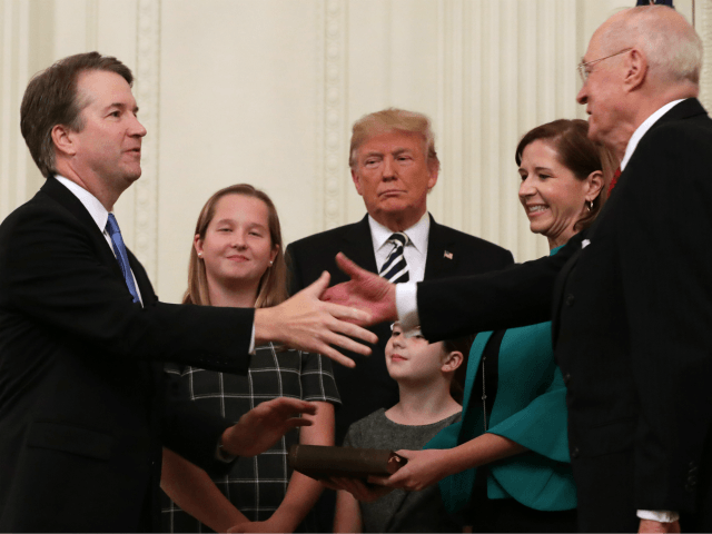 WASHINGTON, DC - OCTOBER 08: U.S. Supreme Court Associate Justice Brett Kavanaugh (L) shakes hands with retired Justice Anthony Kennedy after Kavanaugh's ceremonial swearing in with his wife Ashley, youngest daughter Liza, oldest daughter Margaret and President Donald Trump in the East Room of the White House October 08, 2018 …