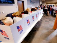 A growing line of voters, right, wait as others fill out their paper ballots in privacy voting booths, Tuesday, Nov. 6, 2018, in Ridgeland, Miss. Voters have a number of races to consider, including judiciary and federal offices and some local issues. (AP Photo/Rogelio V. Solis)