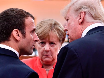 TOPSHOT - US President Donald Trump (R), French President Emmanuel Macron (L) and German Chancellor Angela Merkel (C) chat at the start of the first working session of the G20 meeting in Hamburg, northern Germany, on July 7, 2017. Leaders of the world's top economies will gather from July 7 …