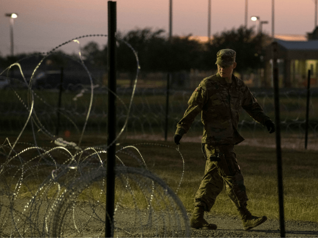 A US Army soldier closes a razor-wire gate at a compound where the military is erecting an encampment near the US-Mexico border crossing at Donna, Texas, on November 6, 2018. (Photo by Andrew Cullen / AFP) (Photo credit should read ANDREW CULLEN/AFP/Getty Images)