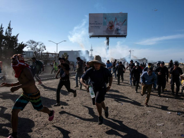 Central American migrants run along the Tijuana River near a border crossing after Border Patrol agents used tear gas on November 25, 2018. Guillermo Arias/AFP/Getty Images
