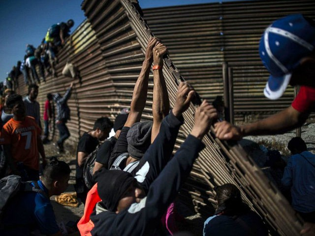 TOPSHOT - A group of Central American migrants -mostly Hondurans- climb the border fence between Mexico and the United States as others try to bring it down, near El Chaparral border crossing, in Tijuana, Baja California State, Mexico, on November 25, 2018. - Hundreds of migrants attempted to storm a …