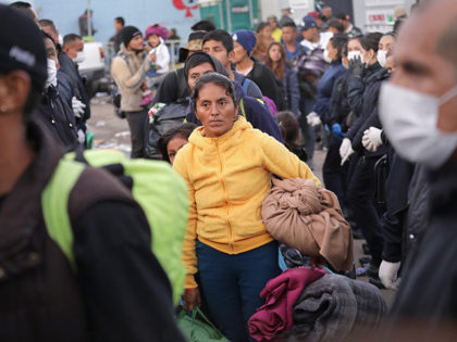TIJUANA, MEXICO - NOVEMBER 30: Police funnel members of the migrant caravan to a bus to be transported to a new temporary shelter on November 30, 2018 in Tijuana, Mexico. Authorities closed a squalid open-air shelter next to the U.S.-Mexico border fence and bussed thousands of migrants to a different …