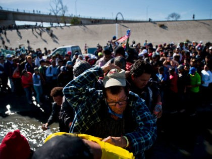 Migrants cross the river at the Mexico-U.S. border after pushing past a line of Mexican police at the Chaparral crossing in Tijuana, Mexico, Sunday, Nov. 25, 2018, as they try to reach the U.S. The mayor of Tijuana has declared a humanitarian crisis in his border city and says that …