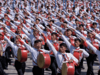 Students march past a balcony from where North Korea's leader Kim Jong Un was watching, during a mass rally on Kim Il Sung square in Pyongyang on September 9, 2018. - North Korea held a military parade to mark its 70th birthday, but refrained from showing off the intercontinental ballistic …