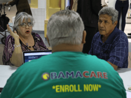 Isabel Diaz Tinoco (L) and Jose Luis Tinoco speak with Otto Hernandez, an insurance agent from Sunshine Life and Health Advisors, as they shop for insurance under the Affordable Care Act at a store setup in the Mall of Americas on November 1, 2017 in Miami, Florida. The open enrollment …