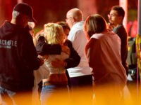 "People comfort each other as they stand near the scene Thursday, Nov. 8, 2018, in Thousand Oaks, Calif., where a gunman opened fire Wednesday inside a country dance bar crowded with hundreds of people on ""college night,"" wounding multiple people including a deputy who rushed to the scene. (AP Photo/Mark …"