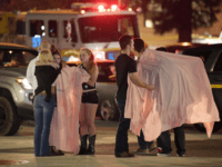 "People comfort each other as they sit near the scene Thursday, Nov. 8, 2018, in Thousand Oaks, Calif. where a gunman opened fire Wednesday inside a country dance bar crowded with hundreds of people on ""college night,"" wounding 11 people including a deputy who rushed to the scene. Ventura County …"