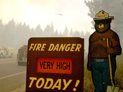 SOUTH LAKE TAHOE, CA - JUNE 26: A Smokey the Bear sign is seen as firefighters battle the Angora fire as it approaches homes June 26, 2007 in South Lake Tahoe, California. Firefighters continue to battle the 2,700 acre Angora wildfire near Lake Tahoe that has consumed over 200 structures. …