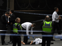 A police officer (C) inspects a body at the crime scene following a stabbing incident in Melbourne on November 9, 2018. - A knife-wielding attacker killed one person and injured two others in a rush hour stabbing rampage in downtown Melbourne on November 9, before being shot and captured by …