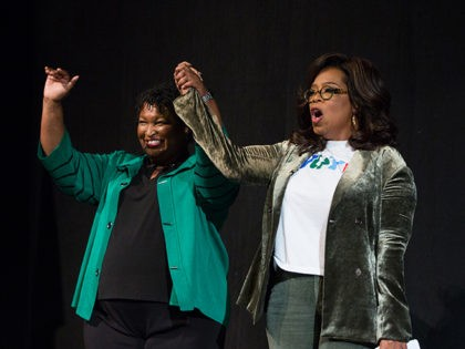 MARIETTA, GA - NOVEMBER 01: Oprah Winfrey and Georgia Democratic Gubernatorial candidate Stacey Abrams greet the audience during a town hall style event at the Cobb Civic Center on November 1, 2018 in Marietta, Georgia. Winfrey travelled to Georgia to campaign with Abrams ahead of the mid-term election. (Photo by …