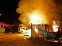Israeli security forces and firefighters gather near abuilding set ablaze after it was hit by a rocket fired from the Palestinian enclave, in the southern Israeli town of Sderot on November 12, 2018. - Israel's military said it was carrying out air strikes 'throughout the Gaza Strip' on Monday after …