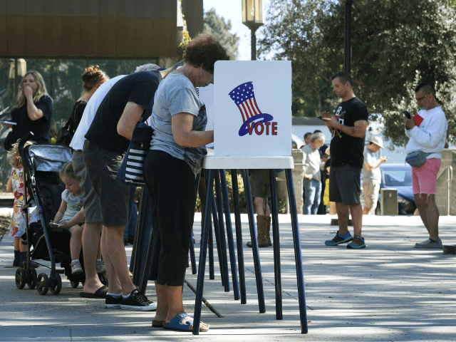 People vote at outdoor booths during early voting for the mid-term elections in Pasadena, California on November 3, 2018. (Photo by Mark RALSTON / AFP) (Photo credit should read MARK RALSTON/AFP/Getty Images)