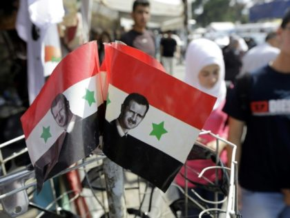 Syrians walk past Syrian national flags bearing President Bashar al-Assad's portrait in Damascus on May 11, 2014