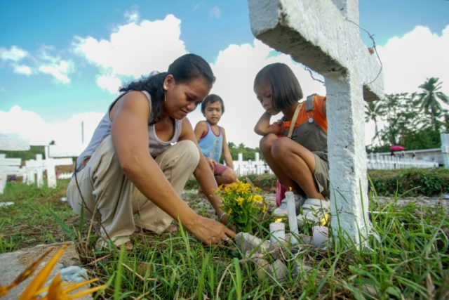 In Tacloban, the worst-hit city, residents painted gravestones, laid flowers and lit candles at a cemetery in memory of the thousands of typhoon dead