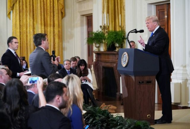 CNN correspondent Jim Acosta (C) was barred by the White House after a testy exchange with President Donald Trump