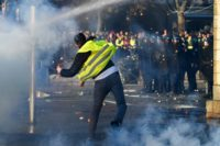 "A demonstrator throws an object at police in Quimper, western France, at a rally for the ""yellow vests"" movement, named for the high-visibility jackets worn by supporters"