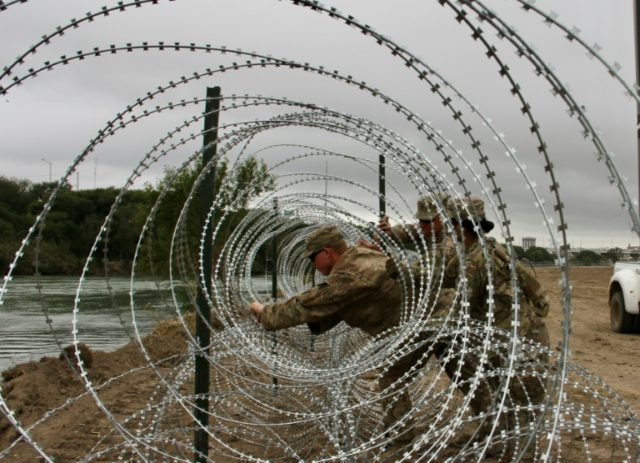 Soldiers from the Kentucky-based 19th Engineer Battalion installing barbed wire fences on the banks of the Rio Grande in Laredo, Texas