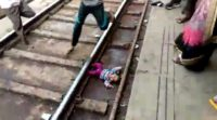 This screengrab taken from a video shot and provided by NNIS shows a baby girl next to train tracks after being dropped in the station in Uttar Pradesh state