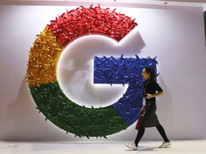 In this Monday, Nov. 5, 2018, photo, a woman carries a fire extinguisher past the logo for Google at the China International Import Expo in Shanghai. Internet traffic hijacking disrupted several Google services Monday, Nov. 12, 2018, including search and cloud-hosting services. (AP Photo/Ng Han Guan)