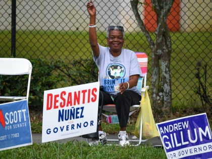 ORLANDO, FLORIDA - NOVEMBER 04: Campaigners hold placards outside an early voting station at West Kaley Street on November 4, 2018 in Orlando, Florida. U.S. Sen. Bill Nelson (D-FL), who was campaigning in the area, and outgoing Republican Florida Gov. Rick Scott are in a virtual dead heat just two …