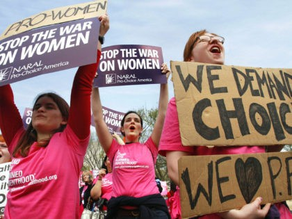 Erica Moses, 21, of Bethlehem, Pa., left, Rachel Graf Evans, 20, of Westtown Pa., and Hope Rehak, 21, of Chicago, take part in a rally in support of Planned Parenthood, Thursday, April 7, 2011, on the National Mall in Washington. (AP Photo/Jacquelyn Martin)