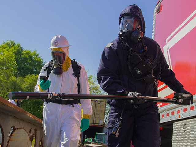 Service members from the 24th Civil Support Team and the U.S. Coast Guard Atlantic Strike Team conducts a 360-degree perimeter patrol to check the radiation levels of a simulated collapsed building at the Urban Search and Rescue Yard in Baltimore, during Vigilant Guard 18 on May 9, 2018. The team, …