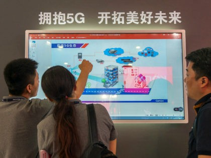 People watch a screen showing information on 5G technology during the Mobile World Conference in Shanghai on June 27, 2018. (Photo by - / AFP) / China OUT (Photo credit should read -/AFP/Getty Images)