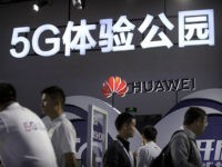 Visitors look at a display for 5G wireless technology from Chinese technology firm Huawei at the PT Expo in Beijing, Wednesday, Sept. 26, 2018. The government-organized event comes amid a mounting tariff war with Washington over Beijing's plans for state-led creation of its own global technology competitors. (AP Photo/Mark Schiefelbein)